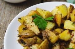 Ofenkartoffeln mit Soße auf einer weißen Platte Stockfotos