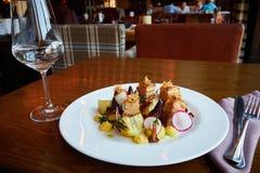 Ofenkartoffelscheiben und -rote Rüben mit Gemüse und Schweinebratenspeck auf dunklem Holztisch dienten im Restaurantinnenraum lizenzfreie stockfotos