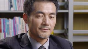 Oferta asiática del negocio de la lectura del ejecutivo empresarial almacen de metraje de vídeo