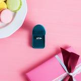 Oferta de la boda, caja que dan el anillo, los macarrones y el regalo en fondo rosado Foco selectivo, visión superior, imagen ent Imagen de archivo