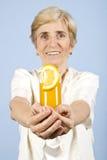 Oferta mayor feliz de la mujer al vidrio con el zumo de naranja Foto de archivo libre de regalías