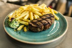 Oferta piec na grillu porterhouse stek słuzyć z chrupiącymi złotymi Francuskimi dłoniakami, świeżą zieloną zielarską sałatką i BB Zdjęcia Stock