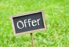 Oferta - quadro com texto no fundo da grama verde Imagens de Stock Royalty Free