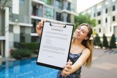 Ofertas hermosas jovenes de la mujer para firmar el contrato Foco en el documento fotos de archivo libres de regalías
