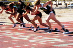 Off the Blocks. The start of the woman's 100 meter dash at a college track meet. motion blur Royalty Free Stock Image