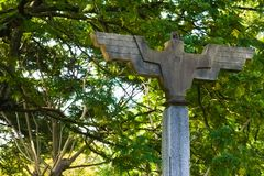 An off-centered shot of an old, bird shaped, outdoor, cement lighting post., with a wide wing span, located in a Thai public park. An off-centered frontal shot royalty free stock images
