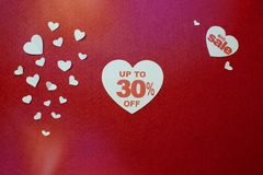 30% off discount promotion sale in big heart on the red background of white hearts. Selling promotion offer percent discount stock photo