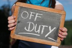 OFF DUTY. Written with chalk on slate shown by young female Stock Photo