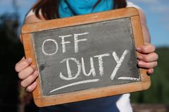 OFF DUTY. Written with chalk on slate shown by young female Royalty Free Stock Image