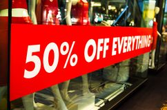 50% off everything sale red sign on shop front glass window. A 50% off everything sale red sign on shop front glass window stock photo