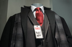 70% off. Mannequin with black coat, 3-piece suit, scarf, red tie and Sale 70% off tag royalty free stock photography