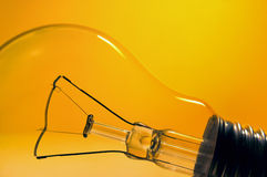 Off peak electricity. Light bulb in front of yellow and orange colored background - Off peak electricity Stock Photography