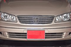 An off-peak vehicle license plate which is red in color. A photo taken on an off-peak vehicle license plate which is red in color at the front of a car in royalty free stock photos