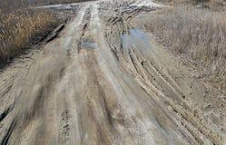 Off-piste Οι βαθιές λαστιχένιες διαδρομές στο δρόμο καλύπτονται με την υγρή βρώμικη άμμο, πλαϊνή Ίχνη ροδών στο ρύπο impassable δ στοκ φωτογραφία με δικαίωμα ελεύθερης χρήσης