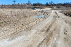 Off-piste Οι βαθιές λαστιχένιες διαδρομές στο δρόμο καλύπτονται με την υγρή βρώμικη άμμο, πλαϊνή Ίχνη ροδών στο ρύπο impassable δ στοκ εικόνες