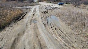 Off-piste Οι βαθιές λαστιχένιες διαδρομές στο δρόμο καλύπτονται με την υγρή βρώμικη άμμο, πλαϊνή Ίχνη ροδών στο ρύπο impassable δ στοκ φωτογραφίες