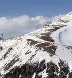 Off-piste helling met stenen en stoeltjeslift in weinig sneeuwjaar Stock Foto's