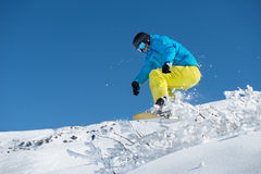 Off-piste riding. Snowboarder jumping over the snowy shrub while off-piste  riding Stock Photography