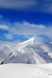 Off-piste slope and blue sky with clouds at sunny day Royalty Free Stock Images