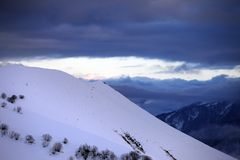 Off-piste slope and cloudy sky at sunset Royalty Free Stock Photos