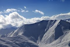 Off piste slope in evening with sunlit clouds Stock Photo