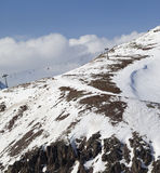 Off-piste slope with stones and chair-lift in little snow year Stock Photos