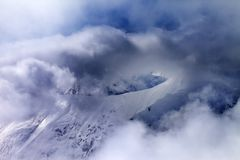 Off-piste slope in sunlight multicolor clouds Stock Photo