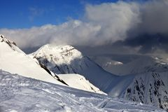 Off-piste slope and sunlit mountains in clouds Royalty Free Stock Images