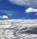 Off-piste slope with track from ski and snowboard and blue sky w Royalty Free Stock Photo