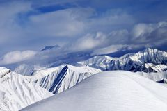 Off-piste snowy slope and cloudy mountains Royalty Free Stock Photos