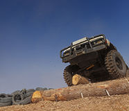 Off road. Car passing a tree trunk obstacle during a competition Stock Image