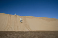 Off Road 4x4 adventure, Namib Desert. 4x4 vehicles driving down giant sand dunes \'dune bashing\', Namib Desert Stock Images