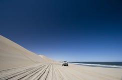Off Road 4x4 adventure, Namib Desert, Namibia. 4x4 vehicle driving along the edge of the desert where the sand meets the Atlantic Ocean. Namib Desert, Namibia Stock Photos