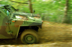 Off-road Action. Military off-road vehicle storming down a forest dirt road. Long exposure time and panning technique were used to create dramatic motion blur Stock Images
