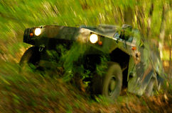Off-road Action. Military off-road vehicle storming through forest, ripping vegetation. Long exposure time was used to create dramatic motion blur effect, focus Royalty Free Stock Photos