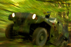 Off-road Action. Military off-road vehicle storming through forest, long exposure time was used to create dramatic motion blur effect Royalty Free Stock Photo