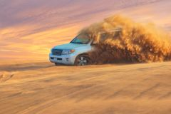 Off-road adventure with SUV in Arabian Desert at sunset. Visit Dubai. Off-road adventure with SUV in Arabian Desert at sunset. Offroad vehicle bashing through stock image