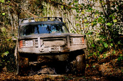 Off-road autumn trip #3. Off-road car with spinning wheels jumps towards onlooker during autumn forest trip Stock Images