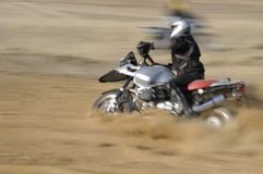 Off-road biker - motion blured. Biker riding his motorcycle off-road through loose sand Stock Photography