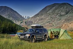 Off-road car camping with a. Tent among the mountains and clear blue sky Stock Image