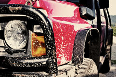 Off-road car covered in mud. A red 4x4 off-road car covered in mud Royalty Free Stock Photography