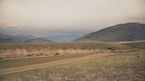 Off-Road Car Fast Driving Across A Flat Dusty Field With Hills And Mountains On The Background In Daytime stock video