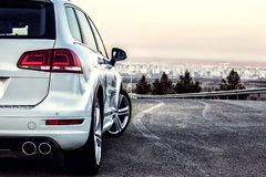 Off-road car Volkswagen Touareg in white without logos on a winding mountain road. Off-road car without logos on a winding mountain road. The photo is suitable royalty free stock image