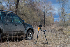 Off-road car, metal detector and shovel in the field Stock Image