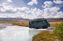 Off-road car moving mountain river at a ford on the background of snow peaks royalty free stock image