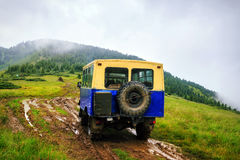 Off-road car rides on the swamp road in the mountains at rain weather, Carpathians, Ukraine. Stock Photography