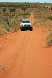 Off road car on rough road. Red Australian rural road with approaching white off road car. Northern Territory, Australia Royalty Free Stock Photos