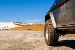 Off road 4x4 car in the snowy mountains on a sunny day. Off-road traveling, all terrain vehicle in nature stock image
