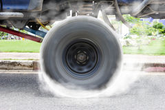 Off-road car spinning wheel burns rubber on floor royalty free stock photo