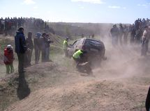 Off-road competition assistants help the car to overcome the obstacle next to the crowd of spectators royalty free stock photography